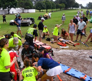 Spectators are tended to after a lightning strike on the East Lake Golf Club course left several injured during a weather delay in the third round of the Tour Championship golf tournament. (AP Photo/John Amis)