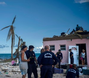 Randy Nagy, center, talks with firefighters arriving from the city of Miami to help those affected by Hurricane Dorian while his wife Silvia, 63, goes out the door of his destroyed house in Pelican Point, Grand Bahama, Bahamas, Monday, Sept. 9, 2019. (AP Photo/Ramon Espinosa)