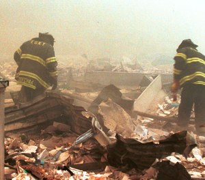 Firefighters sift through wreckage from the World Trade Center on Sept. 11, 2001. (Photo/AP, 1203865Globe, MediaPunch, IPX)