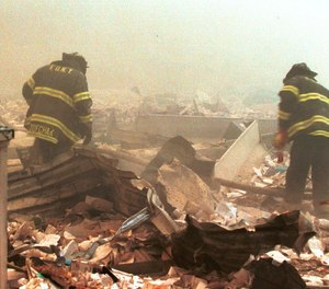 Firefighters sift through wreckage from the World Trade Center on Sept. 11, 2001.