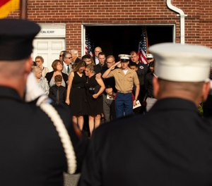 Kiersten Haub, center left, hugs her mother Erika Starke, center, as Michael Haub, center right, salutes for New York firefighter Michael Haub, as they attend a second funeral service for him in Franklin Square, N.Y.  (Photo/AP, Eduardo Munoz Alvarez)