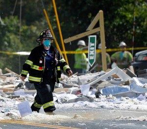 A firefighter walks through the scene of the LEAP building explosion that killed Farmington Fire Capt. Michael Bell and injured seven others on Monday, Sept. 16, 2019, in Farmington, Maine. Two companies have been fined for safety violations in connection with the deadly blast. (AP Photo/Robert F. Bukaty)