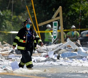A firefighter walks through the scene of the LEAP building explosion that killed Farmington Fire Capt. Michael Bell and injured seven others on Monday, Sept. 16, 2019, in Farmington, Maine. Two companies have been fined for safety violations in connection with the deadly blast.