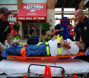 Emergency medical personnel load a simulated victim on a gurney during a mass casualty training exercise, Thursday, Sept. 19, 2019, in Cincinnati. (AP Photo/John Minchillo)