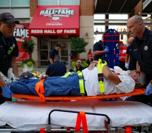 Emergency medical personnel load a simulated victim on a gurney during a mass casualty training exercise, Thursday, Sept. 19, 2019, in Cincinnati.