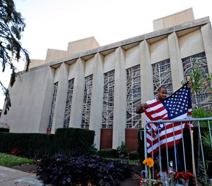A man places an American flag outside the Tree of Life synagogue in Pittsburgh on Sunday, Oct. 27, 2019, the first anniversary of the shooting at the synagogue that killed 11 worshippers.