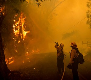 Firefighters battle a wildfire called the Kincade Fire on Chalk Hill Road in Healdsburg, Calif., Sunday, Oct. 27, 2019. (AP Photo/Noah Berger)
