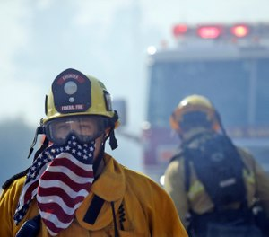 A firefighter covers his face with a U.S. flag scarf as he fights the Easy Fire, Wednesday, Oct. 30, 2019, in Simi Valley, Calif. Fire officials say they're investigating the cause of the fire. (AP Photo/Marcio Jose Sanchez)