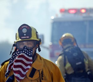A firefighter covers his face with a U.S. flag scarf as he fights the Easy Fire, Wednesday, Oct. 30, 2019, in Simi Valley, Calif. Fire officials say they're investigating the cause of the fire.