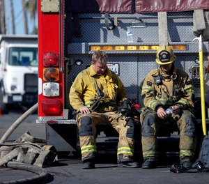 Firefighters rest with their fire truck at outside a cardboard box factory that burned down by a wildfire in Riverside, Calif. Thursday, Oct. 31, 2019. Some Calif. firefighters are turning to meditation, yoga and other therapies to avoid developing stress-related conditions. (AP Photo/Ringo H.W. Chiu)