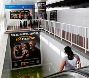 Pedestrians on an escalator pass large posters aimed at curbing sex trafficking, Wednesday, Nov. 6, 2019, at the Metromover Knight Center Station in Miami. Authorities in Miami are launching the initiative in the events surrounding February's Super Bowl. (AP Photo/Wilfredo Lee)