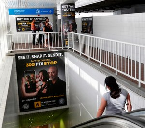 Pedestrians on an escalator pass large posters aimed at curbing sex trafficking, Wednesday, Nov. 6, 2019, at the Metromover Knight Center Station in Miami. Authorities in Miami are launching the initiative in the events surrounding February's Super Bowl.