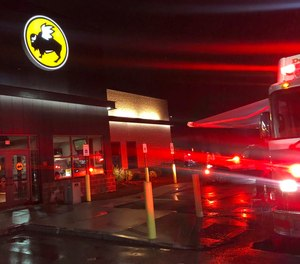 Emergency crews at the Buffalo Wild Wings restaurant in Burlington, Mass. Thursday night, Nov. 7, 2019. Massachusetts authorities say an employee of the restaurant has died and eight others have been hospitalized following a chemical mixture at the restaurant. WHDH-TV reports officials responded Thursday night to reports of a chemical reaction in the kitchen area of the Burlington restaurant where they found a male employee suffering from nausea.