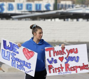 Student Sayla David, 12, holds thank you signs for first responders outside the Saugus High School in Santa Clarita, Calif., Friday, Nov. 15, 2019. (AP Photo/Damian Dovarganes)