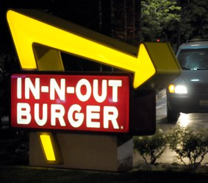 In this June 8, 2010, file photo, a customer receives an order from the drive-through at an In-N-Out Burger in Baldwin Park, Calif. CAL FIRE alleges that fast food chain In-N-Out was responsible for a 2017 wildfire in rural Arroyo Grande, Calif., according to a lawsuit filed in San Luis Obispo Superior Court. (AP Photo/Adam Lau, File)