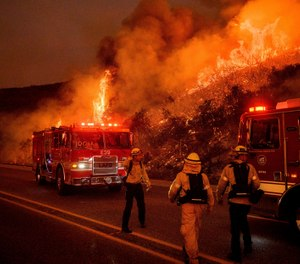 Firefighters battle the Cave Fire burn as it flares up along Highway 154 in the Los Padres National Forest, above Santa Barbara, Calif., Tuesday, Nov. 26, 2019. (AP Photo/Noah Berger)