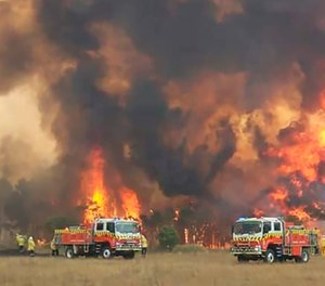 In this image dated Dec. 30, 2019, and provided by NSW Rural Fire Service via their Twitter account, firefighters are seen as they try to protect homes around Charmhaven, New South Wales. Wildfires burning across Australia's two most-populous states Tuesday trapped residents of a seaside town in apocalyptic conditions, destroyed many properties and caused fatalities. (Photo/Twitter@NSWRFS via AP)