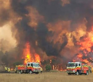 In this image dated Dec. 30, 2019, and provided by NSW Rural Fire Service via their Twitter account, firefighters are seen as they try to protect homes around Charmhaven, New South Wales. Wildfires burning across Australia's two most-populous states Tuesday trapped residents of a seaside town in apocalyptic conditions, destroyed many properties and caused fatalities.