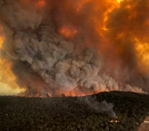In this Monday, Dec. 30, 2019, aerial photo, wildfires rage under plumes of smoke in Bairnsdale, Australia. Two dozen people have been charged with intentionally lighting fires during the crisis that has claimed 25 lives and destroyed 2,000 homes.