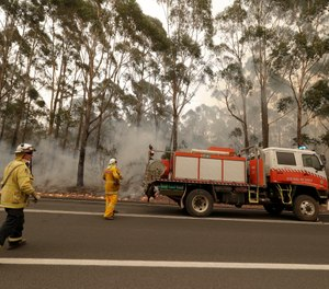 A firefighting crew battles a fire near Burrill Lake, Australia. (AP Photo/Rick Rycroft)