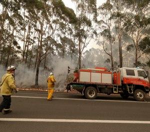 A firefighting crew battles a fire near Burrill Lake, Australia.