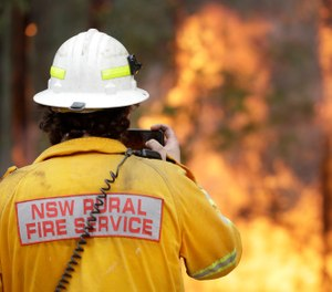 A firefighter uses his phone to record a controlled burn near Tomerong, Australia, Wednesday, Jan. 8, 2020, in an effort to contain a larger fire nearby. (AP Photo/Rick Rycroft)