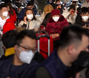Travelers wear face masks as they sit in a waiting room at the Beijing West Railway Station in Beijing, Tuesday, Jan. 21, 2020. A fourth person has died in an outbreak of a new coronavirus in China, authorities said Tuesday, as more places stepped up medical screening of travelers from the country as it enters its busiest travel period. (AP Photo/Mark Schiefelbein)