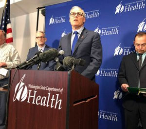 Washington Gov. Jay Inslee, center, speaks Tuesday Jan. 21, 2020, at a news conference in Shoreline, Wash., following the announcement that a man in Washington state is the first known person in the United States to catch a new type of coronavirus that officials believe originated in China. A U.S.-based international standard-setting agency for emergency dispatchers has released guidelines for screening callers for potential exposure to the virus. (AP Photo/Carla K. Johnson)