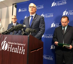 Washington Gov. Jay Inslee, center, speaks Tuesday Jan. 21, 2020, at a news conference in Shoreline, Wash., following the announcement that a man in Washington state is the first known person in the United States to catch a new type of coronavirus that officials believe originated in China. The man who caught the virus is a Washington state resident who returned last week from China and is currently hospitalized near Seattle. (AP Photo/Carla K. Johnson)