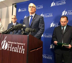 Washington Gov. Jay Inslee, center, speaks Tuesday Jan. 21, 2020, at a news conference in Shoreline, Wash., following the announcement that a man in Washington state is the first known person in the United States to catch a new type of coronavirus that officials believe originated in China. The man who caught the virus is a Washington state resident who returned last week from China and is currently hospitalized near Seattle.