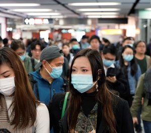 Passengers wear masks to prevent an outbreak of a new coronavirus in a subway station, in Hong Kong, Wednesday, Jan. 22, 2020.