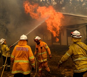 Firefighters battle the Morton Fire as it burns a home near Bundanoon, New South Wales, Australia, on Thursday, Jan. 23, 2020. (AP Photo/Noah Berger)