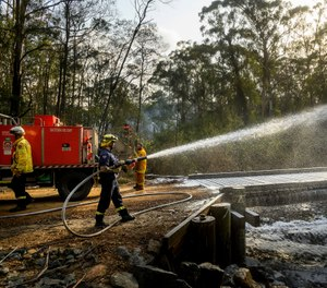 A firefighter coats a bridge with foam as a bushfire burns near Moruya, New South Wales, Australia, Saturday, Jan. 25, 2020. Wildfires destroyed more than 3,000 homes and razed more than 26 million acres since September. (AP Photo/Noah Berger)