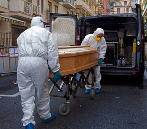 Medical staff wearing protective suits carry the coffin containing the body of a woman who passed away in her room at a hotel in Italy, Sunday March 1, 2020. The woman had tested positive for COVID-19. (AP Photo)