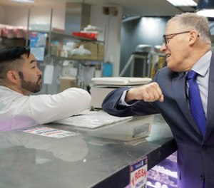 Washington Gov. Jay Inslee, right, bumps elbows with a worker at the seafood counter of the Uwajimaya Asian Food and Gift Market, Tuesday, March 3, 2020, in Seattle's International District. (AP Photo/Ted S. Warren)