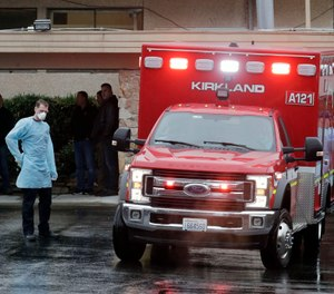 Workers stand near an ambulance, Friday, March 6, 2020, at the Life Care Center in Kirkland, Wash., which has become the epicenter of the COVID-19 coronavirus outbreak in Washington state. (AP Photo/Ted S. Warren)
