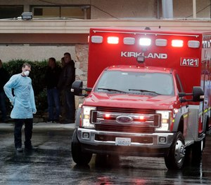 Workers stand near an ambulance, Friday, March 6, 2020, at the Life Care Center in Kirkland, Wash., which has become the epicenter of the COVID-19 coronavirus outbreak in Washington state.