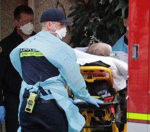 A patient is loaded into an ambulance at a nursing home. (AP Photo/Ted S. Warren)