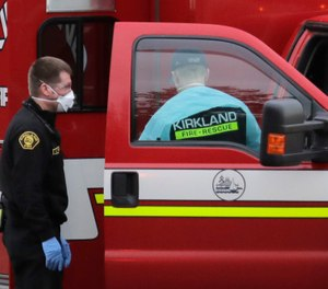 Kirkland Fire and Rescue ambulance workers work near an ambulance after a patient was loaded for transport, Tuesday, March 10, 2020, at the Life Care Center in Kirkland, Wash., near Seattle. (AP Photo/Ted S. Warren)