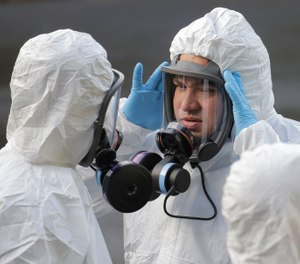 A worker from a Servpro disaster recovery team wearing a protective suit and respirator adjusts his mask before entering the Life Care Center in Kirkland, Wash. to begin cleaning and disinfecting the facility, Wednesday, March 11, 2020, near Seattle. The nursing home is at the center of the outbreak of the COVID-19 coronavirus in Washington state. (AP Photo/Ted S. Warren)