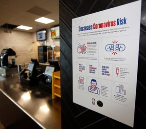 A sign warning about the risks of coronavirus hangs next to a food stand on the main concourse of Pepsi Center before an NHL hockey game between the New York Rangers and the Colorado Avalanche Wednesday, March 11, 2020, in Denver. (AP Photo/David Zalubowski)