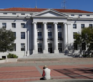 A man sits across from Sproul Hall on the University of California campus in Berkeley, Calif., Wednesday, March 11, 2020.