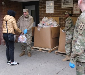 "Members of the New York National Guard distribute food to families in New Rochelle, N.Y., Thursday, March 12, 2020. The area endured a fast-growing COVID-19 cluster, which led to Gov. Andrew Cuomo declaring a 1-mile radius ""containment area"" in the New York suburb. (AP Photo/Seth Wenig)"