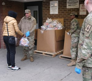 "Members of the New York National Guard distribute food to families in New Rochelle, N.Y., Thursday, March 12, 2020. The area endured a fast-growing COVID-19 cluster, which led to Gov. Andrew Cuomo declaring a 1-mile radius ""containment area"" in the New York suburb."