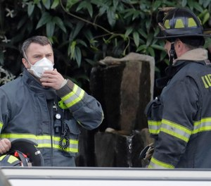 In this March 11, 2020 photo, a Kirkland firefighter wears a mask as he responds to an automatic fire alarm that was accidentally triggered at the Life Care Center in Kirkland, Wash., near Seattle.