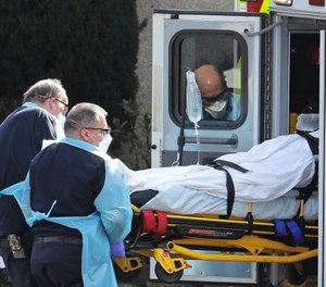 A person is loaded into an ambulance, Thursday, March 12, 2020, at the Life Care Center in Kirkland, Wash., near Seattle. (AP Photo/Ted S. Warren)