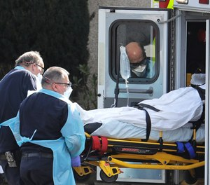 A person is loaded into an ambulance, Thursday, March 12, 2020, at the Life Care Center in Kirkland, Wash., near Seattle.