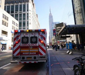 FDNY paramedics place an empty collapsible wheeled stretcher into an ambulance after delivering a patient into the emergency room at NewYork-Presbyterian Lower Manhattan Hospital. (AP Photo/Mary Altaffer)