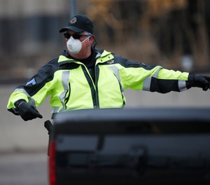 A Denver Police Department officer wears a surgical mask while directing traffic at a coronavirus drive-through testing site outside the Denver Coliseum Saturday, March 14, 2020, in Denver. Officials planned to administer 150 tests but the line of vehicles wrapped around three city blocks.