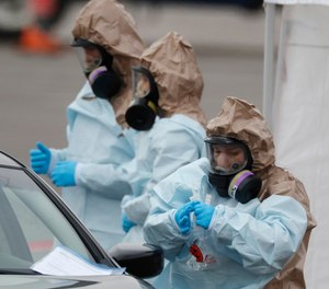 Colorado National Guard medical personnel perform coronavirus test on a motorist at a drive-through testing site outside the Denver Coliseum Saturday, March 14, 2020, in Denver.